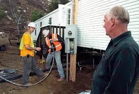 Wildfires] Delzura, CA, December 5, 2007 -- FEMA applicant Jon Grice,  right, watches as electricians Adam