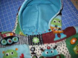 fold down the raw fleece edges on the poncho neck as you go around and pin