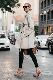 blonde woman wearing club monaco trench coat black sweater black skinny jeans louboutin pumps
