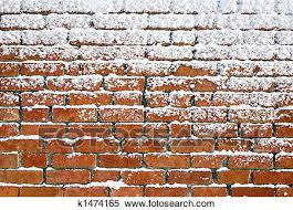 snow sticking to an old brick wall