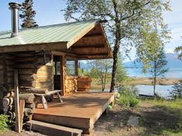 A wooden cabin with a porch is backdropped by water and mountains