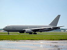boeing kc 46 pegasus gray jet aircraft facing left on apron against a cloudless pale blue sky in