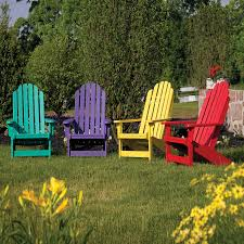fresh green grass and colorful plastic adirondack chairs