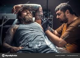 профессиональный татуировщик за работой в студии стоковое фото