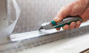cutting excess frosting from window pane