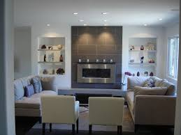 a clean contemporary living room featuring a wall mounted gas burning fireplace accented with floor
