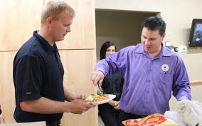 casey pohl general manager of olive garden in grand forks serves food to firefighter