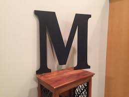 large wood monogram letter m painted black mounted wedding table