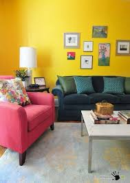 dark green sofa and pink armchair also simply living room table in a bright yellow wall