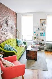 neutral living room with a bold green sofa and red chair that stand out