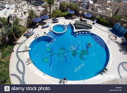 View Over A Swimming Pool From The Balcony Of An Apartment Building