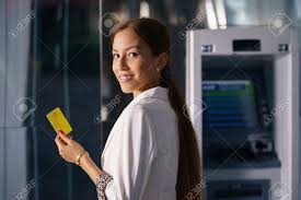 31237566 portrait of latina businesswoman withdrawing dollar from atm cash machine and showing credit card to ifcuifcu