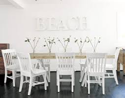 white beach furniture. informal dining room with folding chairs and beach in white letters on the wall furniture