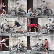 coming up with creative poses with probably the most famous wall mural of them all  on famous wall art in penang with zuji passport top things to do in penang