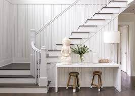 welcoming white foyer features a white lacquered console table positioned over white dip dyed stools against a white paneled wall and accented with a buddha