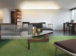 green area rug and brown furniture in living room stock photo