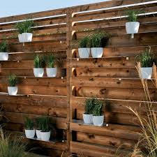 To define a particular living area, there's a wonderfully simple slatted  wood screening system that accepts narrow shelves for planters. - My Garden