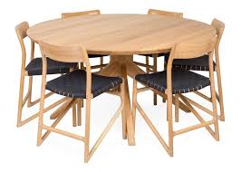 cross round dining table surrounded by fawn chairs
