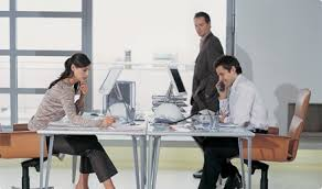 person office desk. Female And Male Person Sitting At Their Office Desk While Another Walks By