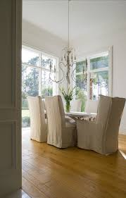 slipcovered dining chairs. Chic Dining Room Features Gray Candle Chandelier Over Trestle Table Surrounded By Linen Slipcovered Chairs As Well
