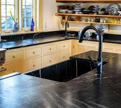 this kitchen island counter top and custom sink is made from classic gray soapstone with a honed finish stove backsplash is from the same material