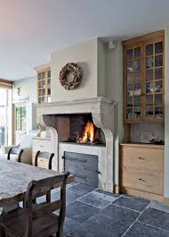 a large fireplace in the kitchen image via building and renovating with reclaimed materials found via belgian pearls