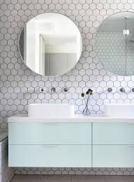 white hex tiles with black grout contrast with mint cabinets