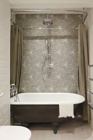 bathroom features gray geometric accent wall fitted with a rainfall shower head alongside a black claw foot bathtub framed by a ceiling mount shower rod
