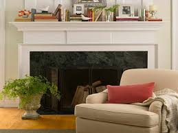 interior black fireplace with white mantel fireplace and silver candle holder also book near green