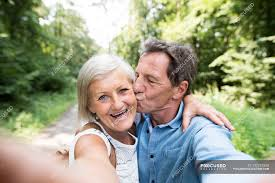active cute senior couple kissing and taking selfie in park stock photos