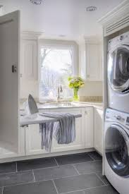 laundry room - grey tile, stacked washer/dryer for smaller space, ironing  board from wall cabinet.