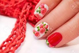 赤フレンチ マニキュアペディキュアの白地にバラのデザイン の写真