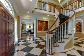 the two story entryway is flanked by a beautiful formal dining room to the right featuring triple arched windows built in china display and detailed