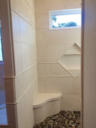 entrance into white travertine tile shower shows the seat niche and window