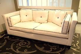 tuxedo style sofa with flared arms and back loose seat and back with side cushions show wood legs and contrast piping