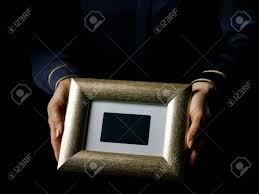 black mania female hands isolated on black background showing a photo frame stock photo