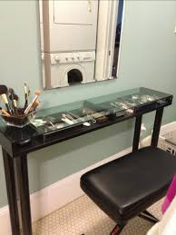 narrow makeup vanity table with storage under glass top and wooden base painted with black color plus brown leather chair seat ideas