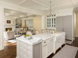 white kitchen island with gray baking island and french candle chandelier