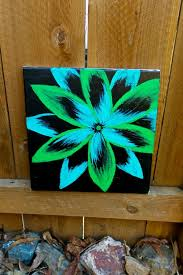 blue and green flower on black background fl by paintzplz