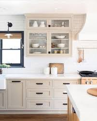 Putty/tan colored kitchen cabinets with white subway tile backsplash ...
