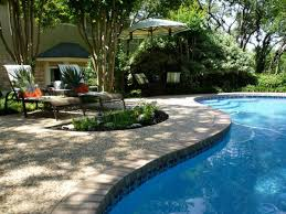 small stone for floor backyard swimming pool design with two lounge chair plus green white umbrella