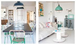 all the white walls and white floors are balanced with bright home decor and accents the furniture is an ecclectic mix of vintage pieces