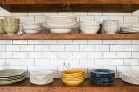 wooden shelves in kitchen on white subway tile backsplash holding stacked dishes stock photo offset