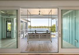 covered deck with swinging sofa and sliding glass doors