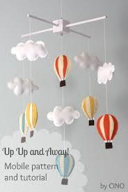 those fluffy clouds and hot air balloons made out of colored felt sheets are hung from dowel ed to a white wooden box which further hangs to the
