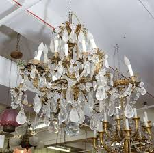 a large elaborate bronze chandelier with vegetal detailing adorned with clear rock crystals