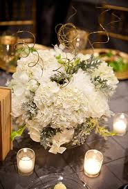 Gold  Tables were decorated with white floral centerpieces ...