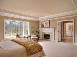 traditional master bedroom with pearl mantels classique wood fireplace mantel surround crown molding carpet
