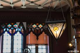 antique colorful glass chandelier in book and large windows in background