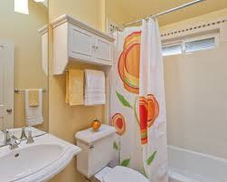 cabinets over toilet in bathroom. inspiration for a transitional subway tile bathroom remodel in seattle with pedestal sink and yellow cabinets over toilet